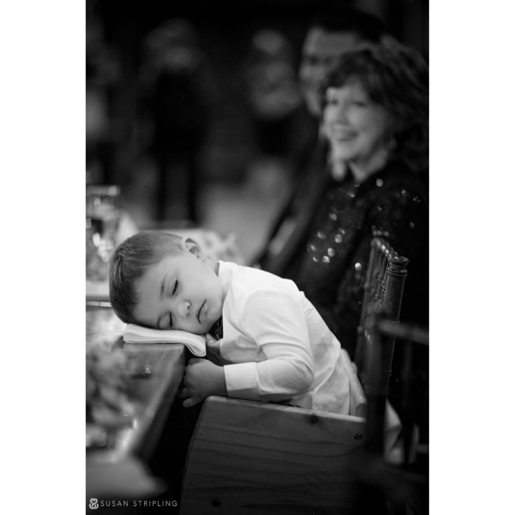 ringbearer asleep at reception table riverside farm